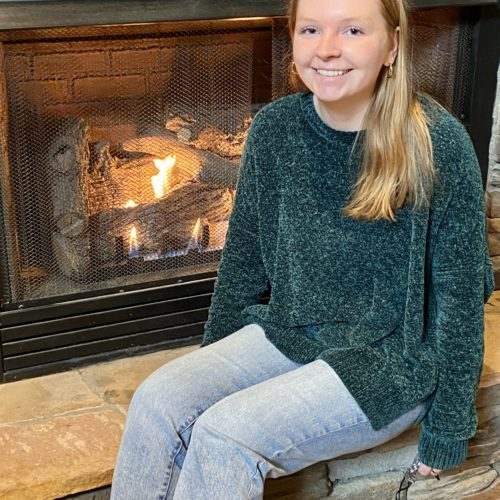 hannah dalness, grandfather vineyard tasting room associate in front of fireplace